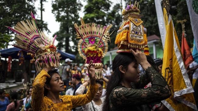 Jika jempana dibawa dengan cara dipikul, sesajen dibawa dengan dijunjung di atas kepala. (Photo by Juni Kriswanto / AFP)