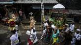 Setelah jempana dan sesaji diletakkan di bibir kolam Pertirtaan, pemangku adat melanjutkan dengan ritual dan sembahyang. (Photo by Juni Kriswanto / AFP)
