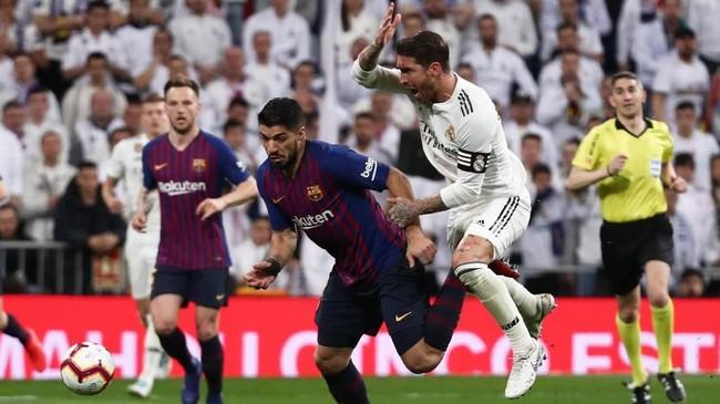 Penyerang Barcelona Luis Suarez berduel dengan kapten Real Madrid Sergio Ramos. Madrid gagal menyamakan kedudukan meski mendominasi penguasaan bola di babak kedua. (REUTERS/Sergio Perez)