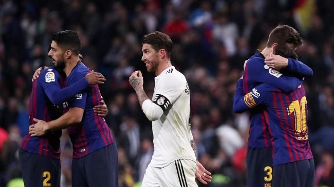 Sergio Ramos berjalan di antara sejumlah pemain Barcelona yang merayakan kemenangan. Barcelona kini unggul sepuluh poin atas Atletico Madrid di puncak klasemen Liga Spanyol. (REUTERS/Sergio Perez)