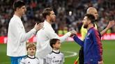 Kapten Real Madrid Sergio Ramos bersalaman dengan kapten Barcelona Lionel Messi sebelum pertandingan. (REUTERS/Juan Medina)