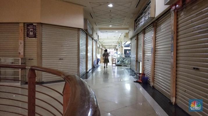 Pengunjung melintas di depan gerai mall di kawasan Jakarta, Senin (4/3/2019). Tingginya biaya pengeluaran, membuat sejumlah gerai ritel menutup tokonya, selain itu maraknya toko online juga disinyalir membuat pergeseran dalam budaya berbelanja masyarakat Indonesia. (CNBC Indonesia/Andrean Kristianto)