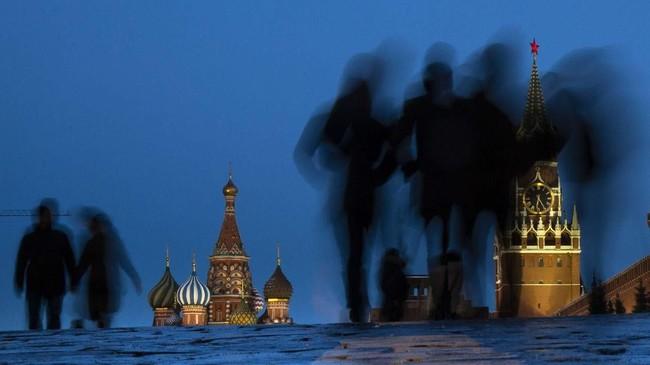 Orang-orang berjalan melewati Red Square setelah matahari terbenam di Moskow, Rusia. St. Basil terlihat di sebelah kiri, sementara Menara Spasskaya di sebelah kanan. (AP/Alexander Zemlianichenko)
