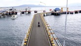 Pekerja melintas di dermaga pelabuhan Ketapang, Banyuwangi, Kamis (7/3). Selama perayaan Nyepi, operasi kapal penyeberangan di Pelabuhan Ketapang dan Gilimanuk ditutup dan baru akan dibuka kembali pada Jumat (8/2) pukul 05.55 WIB. (ANTARA FOTO/Budi Candra Setya)
