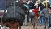 Seorang pria yang menuju Venezuela membawa ban-ban bekas melewati perbatasan dekat Jembatan Internasional Simon Bolivar di La Parada Kolombia. (AP/Martin Mejia)
