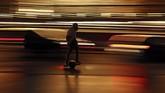 Seorang pria mengendarai seluncur elektrik roda satu melewati markas besar Konsul Eropa di Brussels. (AP/Francisco Seco)