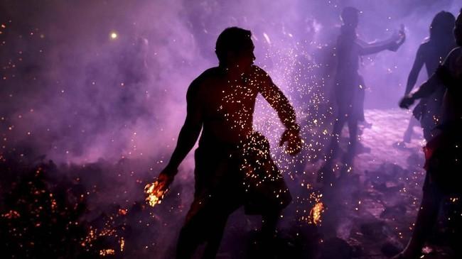 Seorang pria Bali memegang batok kelapa yang terbakar saat berlangsungnya ritual Mesabetan Api, yaitu ritual penyucian yang dilakukan menjelang Hari Raya Nyepi. (Reuters/Johannes P. Christo)