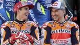 Marc Marquez (kiri) bercanda dengan rekan setimnya di Repsol Honda, Jorge Lorenzo, dalam sesi pemotretan. (KARIM JAAFAR / AFP)