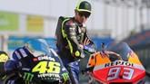 Pebalap Yamaha Valentino Rossi mengamati sepeda motor Honda milik Marc Marquez. (KARIM JAAFAR / AFP)