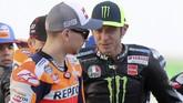 Pebala Yamaha Valentino Rossi (kanan) melihat ke arah pebalap baru Repsol Honda yang juga mantan rekan setimnya di Yamaha, Jorge Lorenzo. (KARIM JAAFAR / AFP)