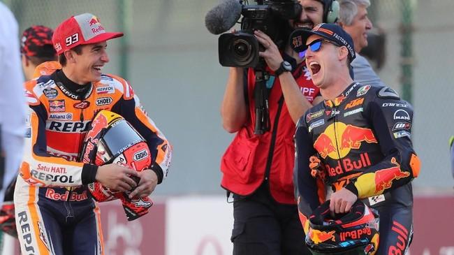 Juara bertahan MotoGP Marc Marquez (kiri) dan pebalap KTM Pol Espargaro bercanda jelang sesi pemotretan. (KARIM JAAFAR / AFP)