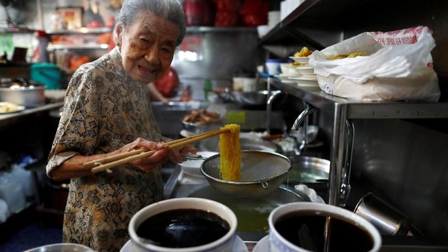 Leong Yuet Meng adalah salah satu penjaja mi kaki lima Singapura. Menariknya, usianya tak lagi muda. Ia sudah berusia 90 tahun. Berjalan saja butuh dibantu. (REUTERS/Edgar Su)