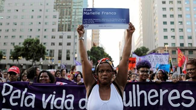 Di Brasil, seorang pengunjuk rasa mengacungkan poster bertuliskan nama Marielle Franco, perempuan aktivis HAM dan anggota dewan yang tewas ditembak. (Reuters/Sergio Moraes)