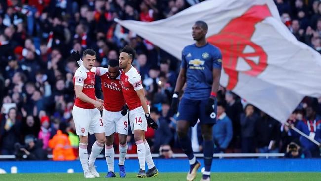 Granit Xhaka, Alexandre Lacazette, dan Pierre-Emerick Aubameyang merayakan gol pertama Arsenal ke gawang Manchester United. (REUTERS/Eddie Keogh)
