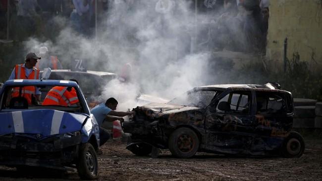 Seorang marshal menggunakan alat pemadam api berusaha mematikan mesin yang terbakar di akhir lomba yang diselenggarakan oleh Association of Motor Sports and Cars, di Ta 'Qali, Malta, pada Minggu (10/3). (REUTERS/Darrin Zammit Lupi)