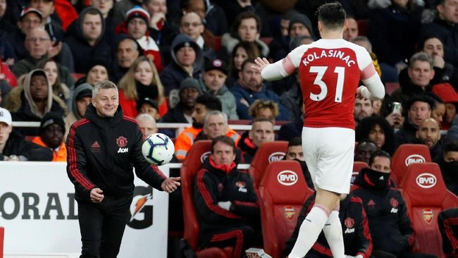 Manajer Man United Ole Gunnar Solskjaer masih berusaha tersenyum ke pemain Arsenal Sead Kolasinac meski timnya tertinggal 0-1 dari tuan rumah. (Reuters/John Sibley)
