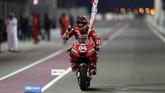 Andrea Dovizioso merayakan keberhasilan memenangi MotoGP Qatar 2019. (Photo by KARIM JAAFAR / AFP)