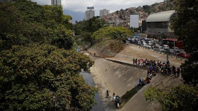 Penduduk Venezuela mengambil air dari sumber terdekat, bahkan selokan dan parit yang airnya tidak bersih. (REUTERS/Carlos Garcia Rawlins)