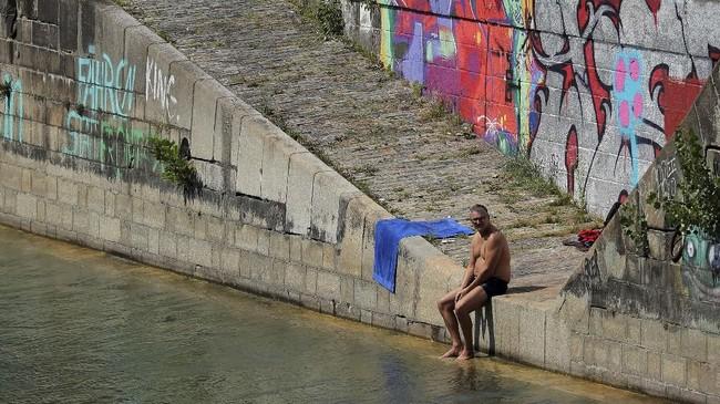 Warga bersantai di kanal Donaukanal, Wina Austria. Sebanyak 1,7 juta orang menghuni Wina. Kota ini memiliki banyak objek wisata yang menjadi magnet kedatangan 6.8 juta turis setiap tahunnya. (REUTERS/Heinz-Peter Bader)