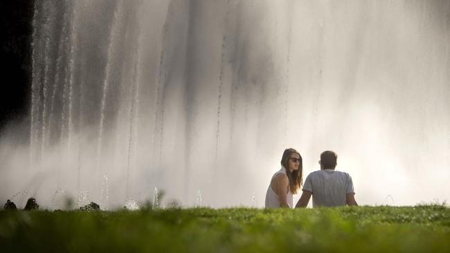 Pasangan bersantai menikmati air mancur di alun-alun Schwarzenberg, Wina, Austria. (JOE KLAMAR / AFP)