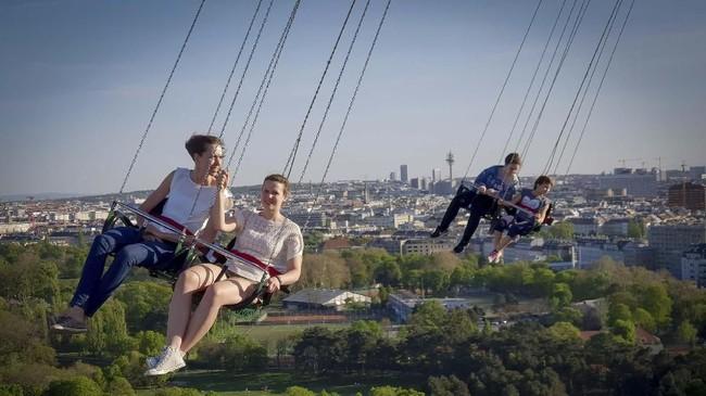 Pengunjung menikmati wahana di Taman Bermain Prater, Wina, Austria.(JOE KLAMAR / AFP)