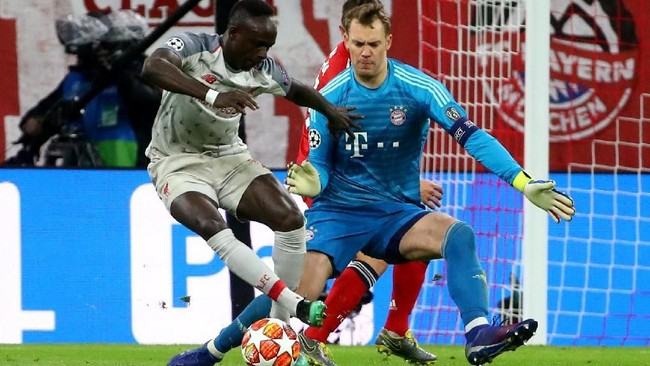 Penyerang Liverpool Sadio Mane mengecoh kiper Bayern Munchen Manuel Neuer sebelum cetak gol pertama ke gawang Munchen pada leg kedua. Ia mencetak dua gol di laga itu. (REUTERS/Michael Dalder)