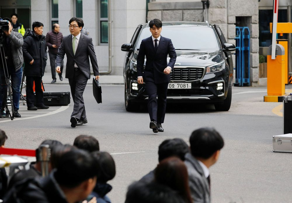 Seungri tiba di kantor kepolisian Seoul pada (14/3/2019) sekitar pukul 14.00 waktu setempat. Seungri tampak memakai jas dengan dasi berwarna hitam. (REUTERS / Kim Hong-Ji)