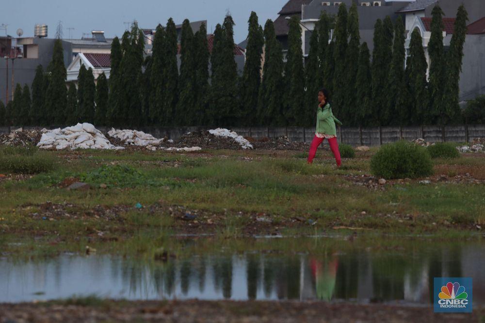 Warga melintas di kawasan yang akan dibangun Stadion Jakarta Internasional Stadium, di eks Taman BMW Jakarta Utara, Kamis (14/3). Pemerintah Provinsi (Pemprov) DKI Jakarta akan memulai pembangunan Jakarta Internasional Stadiumdibekas lahan taman BMW (Bersih Manusiawi Wibawa). (CNBC Indonesia/Muhammad Sabki)