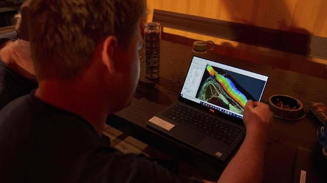Kepala Survey Chief Mike Pownall menjelaskan hasil pemetaan dasar laut menggunakan sonar multi arah dari hasil penjelajahan yang dilakukan Selasa (11/3). (AP Photo/David Keyton)