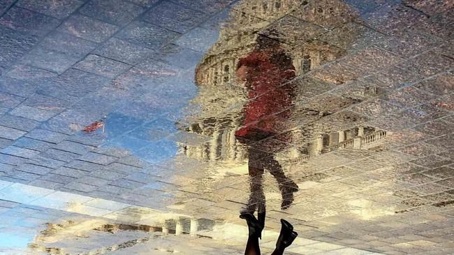 Bayangan seorang perempuan dan juga kubah U.S Capitol di Washington, Amerika Serikat, tercermin di genangan air di bagian timur gedung. (REUTERS/Mary F. Calvert)
