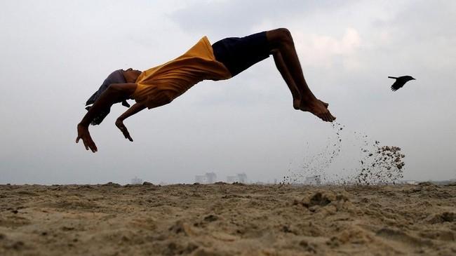 Seorang bocah laki-laki berlatih salto sembari berolahraga di suatu pantai di Kochi, India. (REUTERS/Sivaram V)
