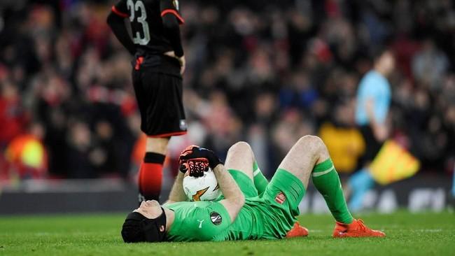 Petr Cech berbaring sambil memegang bola yang digunakan dalam pertandingan antara Arsenal dan Rennes. (Action Images via Reuters/Tony O'Brien)