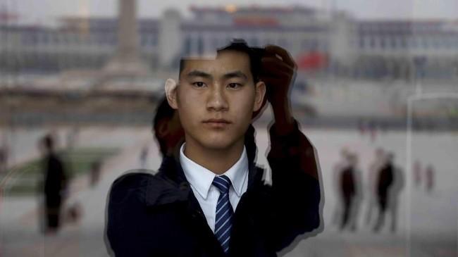 Seorang penjaga keamanan berjaga di balik suatu gelas kaca di gedung dewan di Tiananmen Square. (AP Photo/Ng Han Guan)