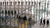 Bayangan orang-orang tercermin di tembok kaca Menara Post, atau markas besar pos dan logistik Jerman, Deutcsche Post DHL, ketika konferensi tahunan digelar di Bonn. (REUTERS/Wolfgang Rattay)