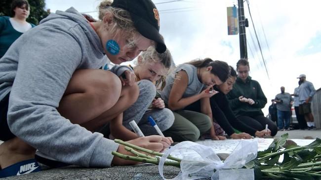 Warga menulis pesan di dekat bunga yang diletakkan di depan Masjid Wellington, Kilbirnie, Wellington, Selandia Baru, Sabtu (16/3/2019). Warga Wellington meletakkan bunga sebagai aksi solidaritas pascapenembakan di dua masjid di Christchurch pada Jumat (15/3). (ANTARA FOTO/Ramadian Bachtiar/wpa)