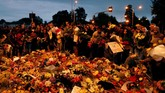 Warga memindahkan bunga-bunga setelah polisi melepas garis polisi di luar masjid Al Noor diChristchurch, Selandia Baru, pada Sabtu (16/3). (REUTERS/Jorge Silva)
