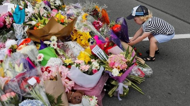Seorang anak kecil menempatkan bunga di lokasi peringatan aksi teror di Selandia Baru di dekat masjid Al Noor diChristchurch, Selandia Baru, pada Sabtu (16/3).(REUTERS/Jorge Silva).