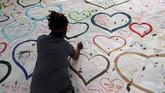 Warga menuliskan rasa simpatiuntuk mengenang korbanpenembakan yang terjadi di masjidAl Noor in Christchurch, Selandia Baru , pada Sabtu (16/3). (REUTERS/Jorge Silva)