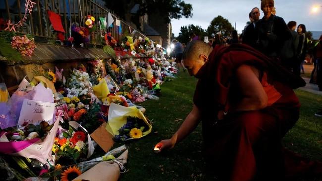 Seorang pria meletakan lilin di karangan bunga yang jadi pusat peringatan aksi teror Selandia Baru di Botanical Gardens in Christchurch, Selandia Baru, pada (16/3). (REUTERS/Edgar Su)