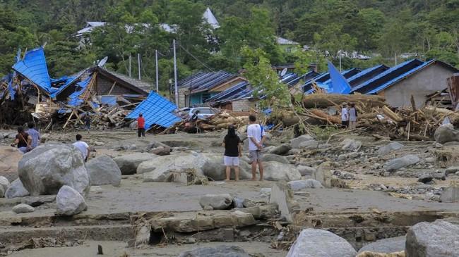 Sejumlah warga berada di dekat helikopter yang bergeser dari tempatnya akibat banjir bandang di Sentani, Kabupaten Jayapura, Papua, Minggu (17/3/2019). (ANTARA FOTO/Gusti Tanati/wpa/ama)