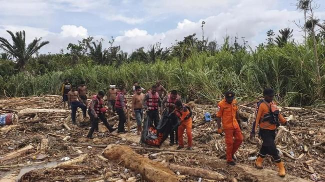 Saat ini, Basarnas masih melakukan evakuasi. Tampak petugas tengah membawa jenazah para korban. (BASARNAS via AP)