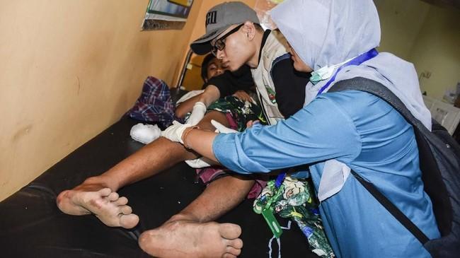 Seorang wisatawan korban selamat tanah longsor akibat gempa bumi mendapatkan perawatan medis oleh petugas di Puskesmas Bayan, Tanjung, Lombok Utara, NTB, Minggu (17/3). (ANTARA FOTO/Ahmad Subaidi)