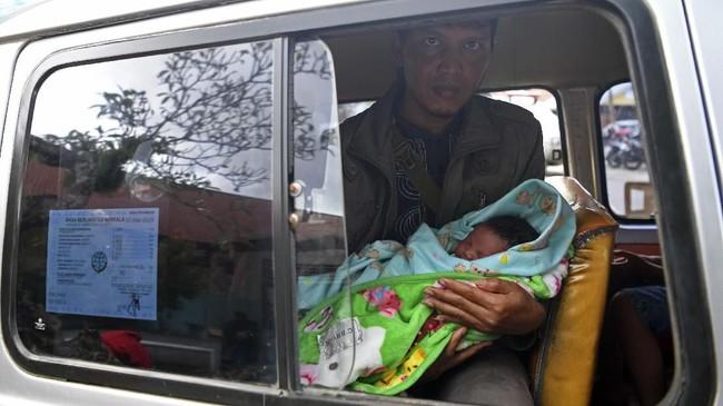 Santoso menunjukan banyinya yang lahir pada Sabtu (16/3) saat peristiwa banjir bandang terjadi di Puskesmas Sentani, Sentani, Jaya Pura, Papua, Senin (18/3/2019). ANTARA FOTO/Zabur Karuru