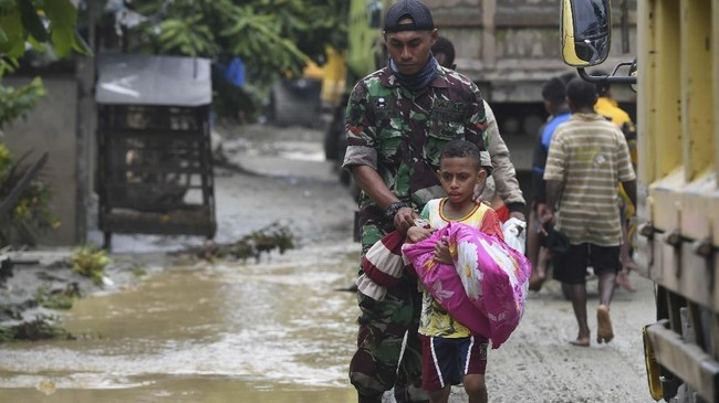 Seorang prajurit TNI menuntun seorang anak yang akan mengungsi akibat banjir bandang di Sentani, Jaya Pura, Papua, Senin (18/3/2019). ANTARA FOTO/Zabur Karuru