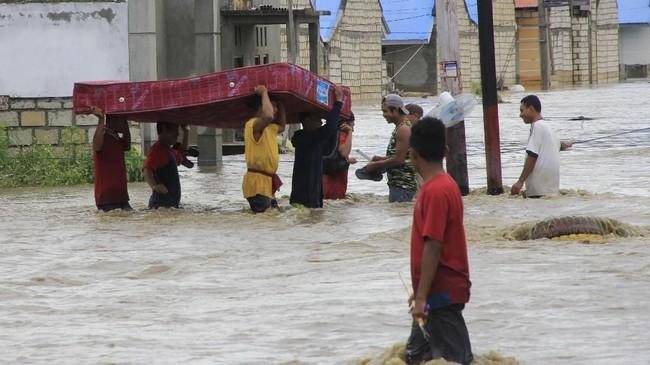 Warga menyelamatkan barang berharga miliknya dari rumahnya yang terendam banjir akibat banjir bandang di Sentani Jayapura, Papua. Saat ini warga korban banjir Sentani membutuhkan bantuan pokok mendasar. ANTARA FOTO/Gusti Tanati