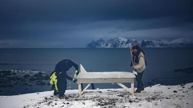 Di tengah dinginnya kawasan Lofotan yang berada dekat Lingkar Arktik, mereka ramai-ramai mengukir bongkahan es menjadi papan surfing. (Olivier MORIN / AFP)