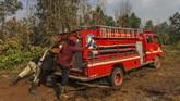 Petugas gabungan dari Pemadam Kebakaran dan BPBD Kota Pekanbaru berusaha mengeluarkan mobil yang terpuruk ketika akan memadamkan kebakaran lahan gambut di Pekanbaru, Riau, 18 Maret 2019.(ANTARA FOTO/Rony Muharrman)