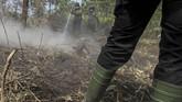 Petugas gabungan dari Polri dan Manggala Agni berusaha memadamkan bara api yang membakar lahan gambut di Pekanbaru. Beberapa lembaga bergabung untuk memadamkan api. (ANTARA FOTO/Rony Muharrman)