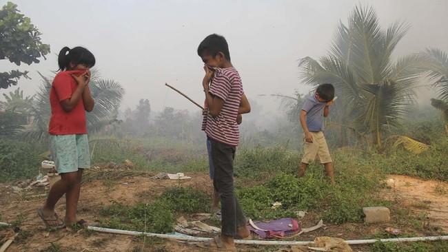 Sejumlah anak bermain sambil menutup hidungnya agar tidak menghirup asap kebakaran lahan di Kecamatan Dumai Timur. Pemerintah setempat sudah menyalurkan masker untuk warga. (ANTARA FOTO/Aswaddy Hamid)