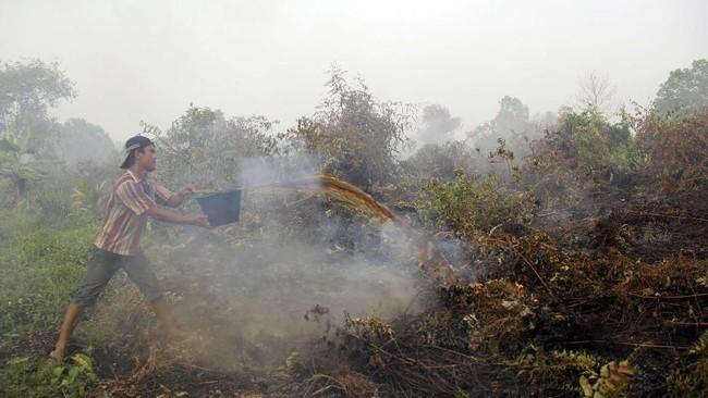 Berbagai cara dilakukan untuk memadamkan api, termasuk dengan cara tradisional. Tampak seorang warga memadamkan api yang membakar lahan dekat permukiman warga di Kecamatan Dumai Timur, Kota Dumai, Riau, Kamis (7/3). (ANTARA FOTO/Aswaddy Hamid)